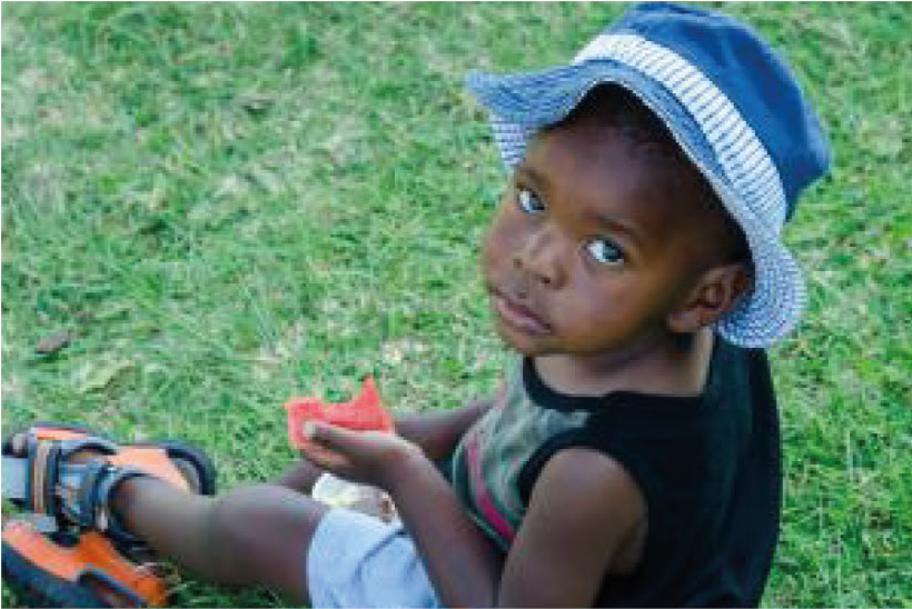 A child with some food sitting on the grass. KET's feeding scheme provides nutritional meals to children in need