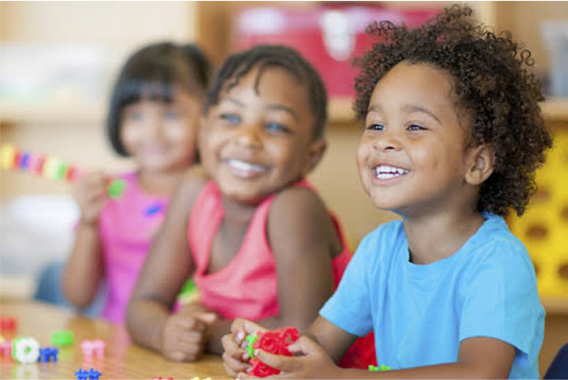 Three children smiling in a classroom. KET's literacy & numeracy programmes give children invaluable skills for education