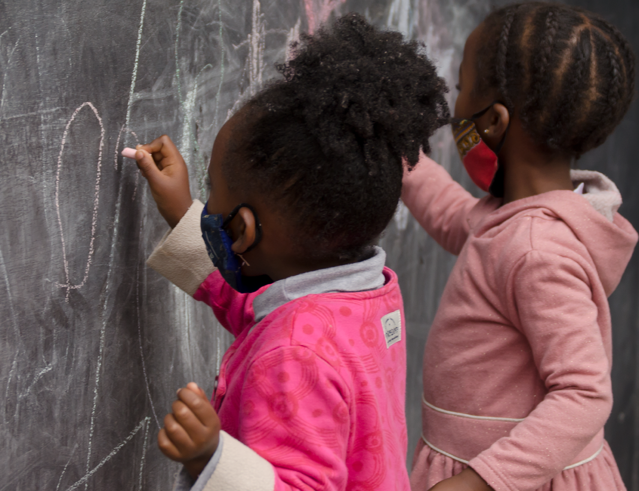 Two children writing on a blackboard in white chalk. KET's education specialists have designed programmes to enhance ECD