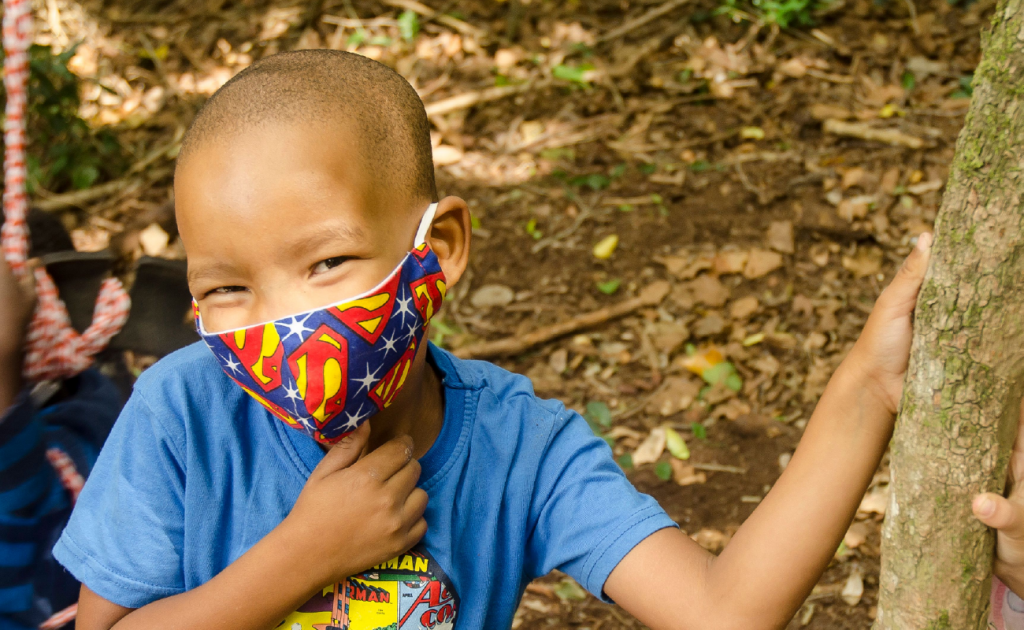 A child in a Superman mask - one of the beneficiaries of the KET volunteer programme