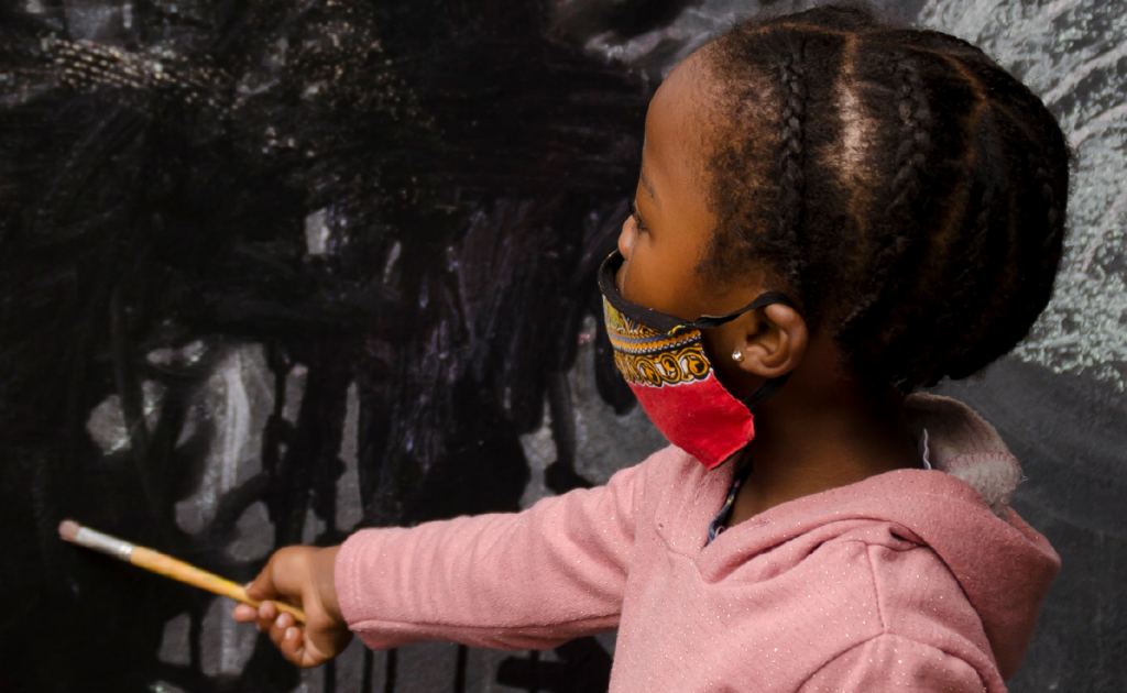 A child in a mask painting in black paint - one of the children who will benefit from ECD volunteer work through KET