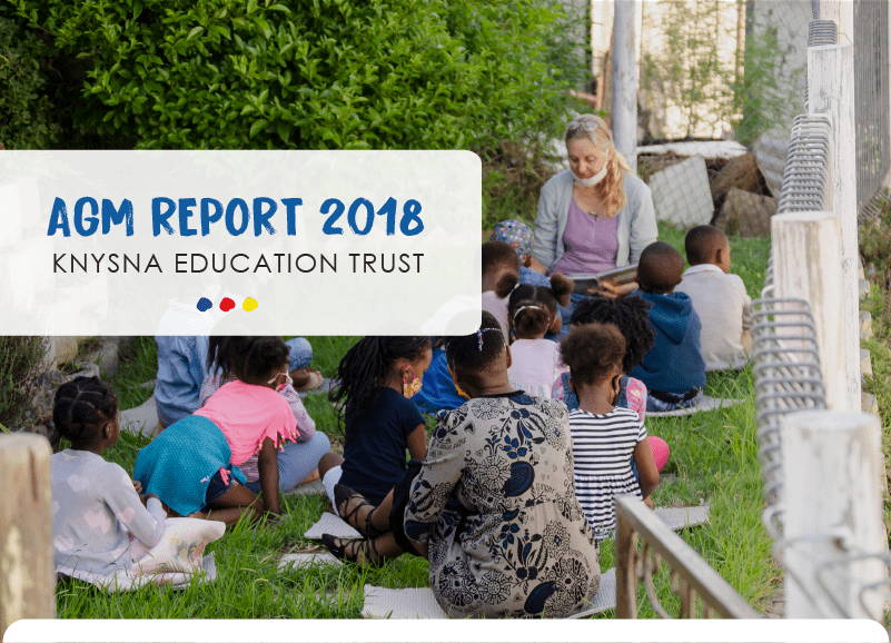 A teacher sitting on the grass with a group of young children - the cover for the Knysna Education Trust's AGM report 2018