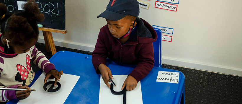Two children sitting in a classroom playing FONIX, KET's literacy programme in South Africa